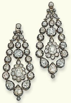 A PAIR OF GEORGE III DIAMOND EAR PENDANTS. Each suspending a pear-shaped drop within an articulated collet surround and foliate surmount set with rose and old-cut diamonds, mounted in silver and gold, some with closed back settings, later diamond collet fitting, circa 1800.