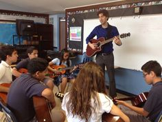 Jamey Arent teaching guitar to students in a Los Angeles-area school. ETM-LA provides instruments for the students free of charge.