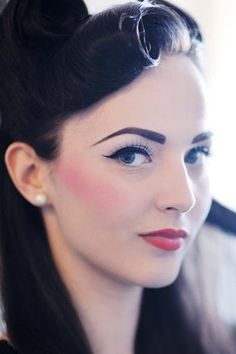 1940's makeup look, classic winged eyeliner, red lip and bold blusher. The eyebrows are also quite polished