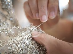 Haute Couture, the making of a dress - fashion atelier; dressmaker embellishing by hand; fashion design behind the scenes