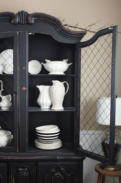 FleaingFrance.com. Pretty vintage cabinet with chicken wire doors and a collection of white stoneware.