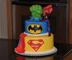 Super Hero Birthday Cake - 2 tiered cake (double layers) coated with Buttercream frosting and covered/decorated with Marshmallow fondant.  Hulk hand is rice krispie treats molded into a fist and covered with marshmallow fondant.