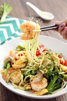 """olive oil cooking spray 3/4 cup broccoli florets (about 5)  1 egg, beaten 3 tsp sesame oil  1/2 tsp freshly minced ginger 1 tsp minced garlic 1/2 red onion, sliced lengthwise into 1/2-inch thick """"strips"""" (fajita-style) 1 small red bell pepper, sliced into 1/2-inch thick """"strips"""" (fajita-style) salt and pepper, to taste 1/4 tsp (or one small pinch) of red pepper flakes 3 tbsp soy sauce 1 tsp honey 1 tsp rice vinegar 3-4 jump shrimp, defrosted, peeled and deveined 1/4 tsp white sesame seeds"""