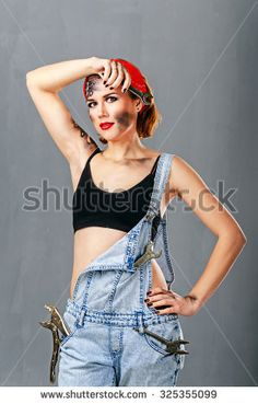 Young girl in denim overalls mechanic holding a wrench and wipes the sweat from her forehead. Professional work. Face art. Jack of all trades. The concept of severe girl. Pin-up girl style.