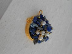 lapis lazuli and fresh water pearls cluster together in gold pendant setting.