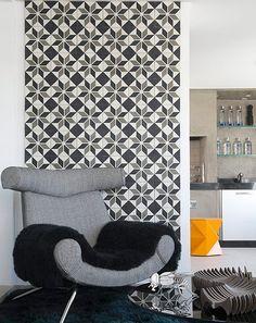 O cantinho da poltrona na casa do designer de interiores Diogo Oliveira ficou mais bacana com o papel de parede de estampa geométrica branca e preta
