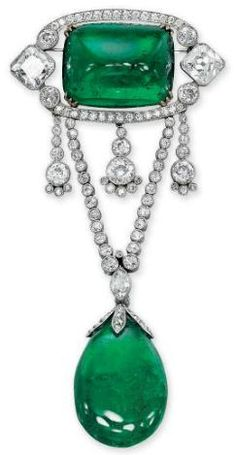 Belle Epoque Emerald and Diamond Brooch, 1910.  The sugarloaf emerald within a diamond frame, suspending three flexible tassels to the V-shaped diamond chain and drop-shaped emerald, circa 1910