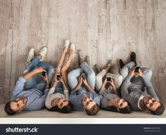 Top view of beautiful young people in casual clothes using smartphones, looking at camera and smiling while sitting together on the floor