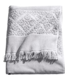 Bath towel in cotton terry with a jacquard-weave pattern, fringe on short sides, and a hanger loop on one long side.