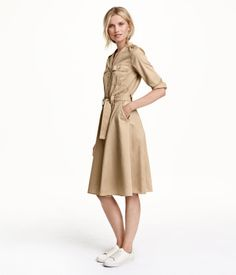 V-neck dress in satin-weave cotton fabric. Buttons at front, shoulder tabs, 3/4-length sleeves, two chest pockets with flap and button, and side pockets. Seam at waist, tie belt, and gently flared skirt. Unlined.