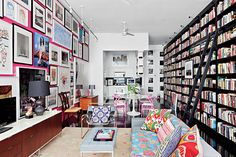 Pink wall covered in art opposite wall all books with bright pink and blue accents throughout