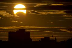 Rare Hybrid Solar Eclipse - photo by Stan Honda;   A partial Solar eclipse is seen just after sunrise over the Queens borough of New York across the East River on Nov. 3, 2013 in New York, New York.