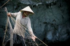 White: A Vietnamese fisherman pulling in his net with the day's catch.