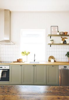 A Brisbane fixer-upper was revived by A Pair and A Spare - Olive green shaker cabinet doors pair beautifully with white tiles, a timber bench top and silver appliances. Wooden Kitchen Cabinets, Green Cabinets, Kitchen Backsplash, Pantry Cabinets, White Cabinets, Kitchen Pantry, Wooden Countertops, Coloured Kitchen Cabinets, Green Kitchen Cupboards
