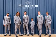 Groomsmen in grey suits posing against blue shed. https://www.facebook.com/HendersonPhotographics