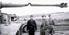 German tank crew member  and officers examine a Panzer tank's 88mm main gun barrel, stuck by an allied round...