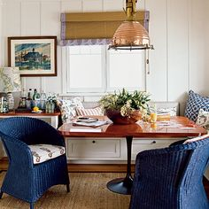 This cottage's dining area has built-in furnishings, like this banquette with storage drawers. | Coastalliving.com