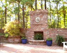 This brick fireplace and terrace are nestled into the surrounding wooded slope by the brick retaining walls. Plantings in the raised planter and the ceramic containers serve to soften and add color the terrace.