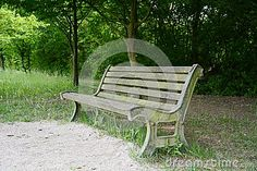 An old rough wooden bench in a park, trees in the background.
