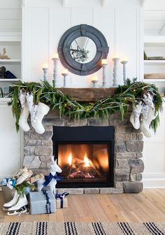 white rustic christmas mantel - Rustic beam and stone fireplace features fresh holiday garland, grey candlesticks and knit stockings