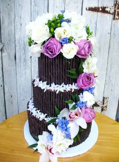 Wedding Cakes: Pirouette cookie decorated wedding cake with purple and blue flowers