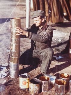 A GI constructs a chimney for his stone house at a 15th AF heavy bomber base in Italy.
