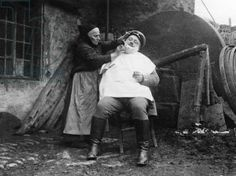 Wife shaving a man in France, 1915