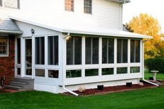 Insulated sunroom with sliding glass windows, glass kneewall and an insulated roof system
