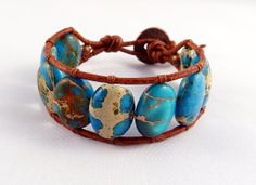Turquoise cuff bracelet featuring large oval blue aqua terra jasper beads in brown leather. This type of jasper has beautiful sand coloured markings running through each gemstone - that's why it's also known as sea sediment jasper.