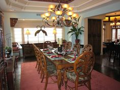 The dining room is one of the best combinations of tropical and Asian styles in the Riverbend home. The cranes atop the antique cabinet, and the tropical setup of the table with the Chinese carving on the ceiling are two beautiful examples of the fusion.