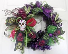 """Sugar Skull wreath, Sugar skull Halloween Wreath, Home decor, halloween decoration, day of the dead, Halloween decor, sugar skulls. Trendy Sugar skulls make up this festive Day of the Dead Halloween Wreath. Perfect accent. Black wreath is filled with sugar skull wired ribbon deco mesh ribbons, purple, green and orange accents and a sugar skull at the base. It measures 18"""" round Comes shipped in a box that can be used for storage from year to year. It measures 18"""" H x 6"""" deep Comes shipped…"""