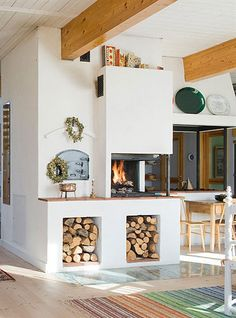 masonry heater. Beautiful.  I love the multiple sides of he fireplace located at the corner...the wood storage underneath is also clever to lift the fire up to a less stooping level. it looks like it has impressive thermal mass, but would it be hard to funnel the heat through the channels?