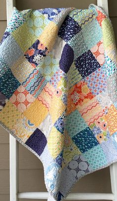 Fun and colorful describes this blue, green, orange, yellow, grey, white, navy quilt, crib quilt, baby quilt machine pieced with 100 percent cotton fabrics by Kate Spain for Moda fabrics called Sunnyside. This colorful fabric collection features large florals, geometries, medallions, leaves, rain drops. Paired with a really cute grey with white polka dots on the back and on the double fold binding, machine sewn on the front and hand sewn to the back for a professional, durable finish, the…