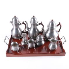 Vintage John Somers pewter coffee and tea service. This service set includes a mahogany tray with pewter handles, one teapot, one coffee pot, one water pitcher, three trivets, a sugar bowl, and creamer. Included with the service is a matching sugar and creamer Newburyport pewter set manufactured by Towle