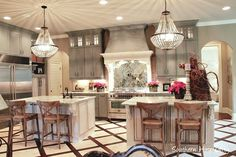 Double islands, crystal chandelier, gray cabinets, stunning kitchen