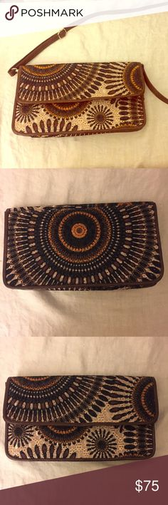Gorgeous unique Patterned crossbody or clutch bag Patterned crossbody bag w/ adjustable brown leather strap & silver buckles/strapholders. Very rare and unique piece. Various Brown, Orange , Amber, and black make a swirly geometric pattern. It also has various other subtle embellishments. Brown leather borders the design/purse. It closes w/ magnetic clasp. One open pocket on the inside as well for tucking strap inside to make clutch. Brown Satin interior. Measures 10 in across, 6 in high, 2…