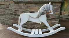 """I spent a day with some yarn and some paint to make this solid wood brown and black (mane and tail were black) rocking horse purchased at a local charity auction event white and gray to match the nursery! I think it was more than worth the effort! Ace Hardware just started carrying a line of chalk paints for crafting that is awesome! I began with a base of white and then used the dark """"antiquing"""" to add some vintage appeal."""