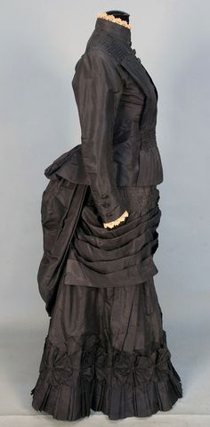 SILK TAFFETA BUSTLE DRESS, 1880's. 2-piece slate grey with peplum bodice having vertical pleats ruched at the shoulder and waist, skirt decorated with bands of ruching, pleats and a band of self pinwheels, lined in brown cotton.