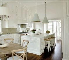 Neutral kitchen.  Pendants.  Range and subtle hood.