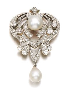 NATURAL PEARL AND DIAMOND BROOCH, EARLY 20TH CENTURY. Designed as an open work scroll plaque accented with circular-cut and rose diamonds, set with natural pearls.