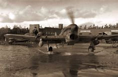 Canadian Hawker Typhoon operating from a very wet former German airfield, February 1945.  The famous ground attack fighter had almost no forward visibility whilst taxiing - hence the airman on the wing.