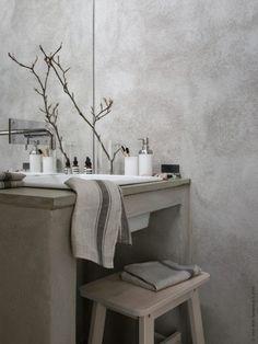 Grått, grenar och ljust trä i badrummet