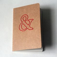 stitched moleskine notebook, red ampersand (lined pages). $9.50, via Etsy.