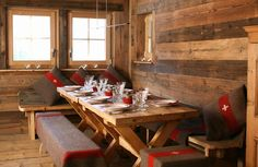 A dining room in a European ski chalet with rustic wood boards on the wall, rustic wood floor, bench style seats around a wood table with red and brown blankets and pillows Chalet Design, Chalet Style, Rustic Wood Floors, Wood Paneling, Ski Lodge Decor, Chalet Interior, Swiss Chalet, Swiss Ski, Interior Decorating