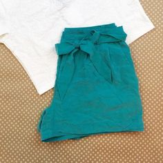 "Teal High-waisted Shorts Super cute high waisted shorts featuring a pleated look, front pockets, faux rear pockets, a cloth tie belt and cuffed hem. Measures 12"" from waist to hem; waist measures 14.5"" laying flat. One belt loop has two tiny tears (pictured) that do not affect the integrity of its function. Make an offer. Divided Shorts"