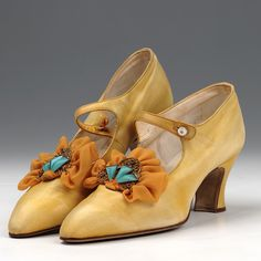 1920's Women's Satin and Crepe Bar Shoes  Pair of yellow satin and crepe bar shoes. Bar with pearl button over instep. Gilt brooch set with blue and red stones and crepe frill sewn on front (not professional probably theatrical trimming) Covered Louis heel.