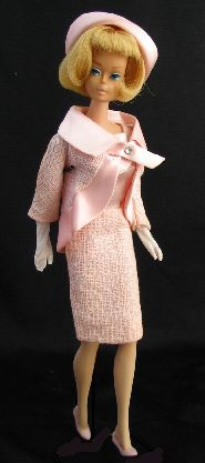 Vintage Barbie Fashion Luncheon #1656 (1966-1967)     Dress with Pink Satin Bodice and Lined Textured Weave Pink Cotton Skirt, Back Zipper  Pink Jacket of Textured Weave Cotton, Pink Satin Collar, Boarder and Jabot and Rhinestone Pin  Rolled Brim Pink Satin Hat with Flowers and Pink Grosgrain Ribbon Inner Headband  Long White Gloves  Pink Closed Toe Heels