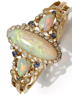 An opal, sapphire and diamond bangle bracelet centering an oval-shaped opal weighing approximately 10.0 carats; remaining opals weighing approximately: 4.50 carats; estimated total diamond weight: 1.25 carats; mounted in eighteen karat gold; diameter: 2 1/16in. (1 diamond deficient)