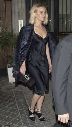 Back to black: As the night grew darker it seemed Jennifer Lawrence's style did too as the actress turned up the heat in a sultry black slip dress when she headed on to The Hunger Games' after-party in Madrid on Tuesday