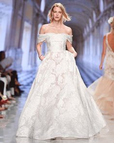 Strapless ball gown in floral organza jacquard with swag sleeves featuring side seam pockets.